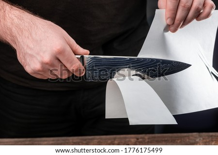 Photo of  Man testing sharpness of knife by cutting a thin sheet of paper. Japanese Gyuto knife with Damascus steel blade.