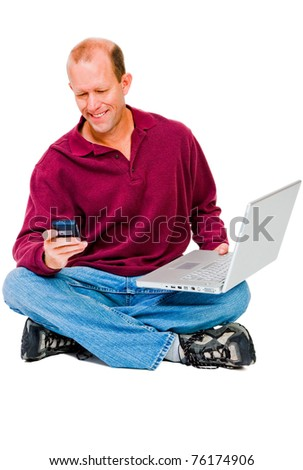 Man text messaging on a mobile while using a laptop