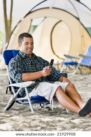 Man text messaging on cell phone at campsite