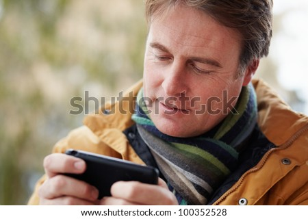 Man Texting On Smartphone Wearing Winter Clothes