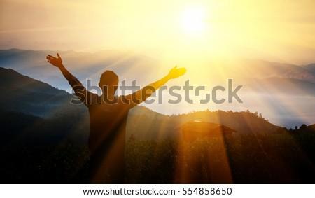 Man thanks God on  mountain. - Shutterstock ID 554858650