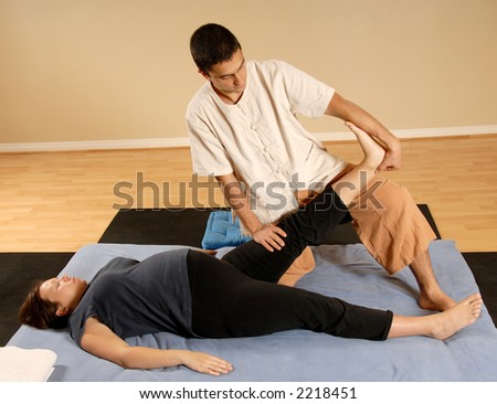 man therapist stretching woman leg in massage