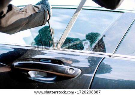 Man thief robbing car on parking.Bandit burglar in criminal scene opening and braking car window on force Zdjęcia stock ©
