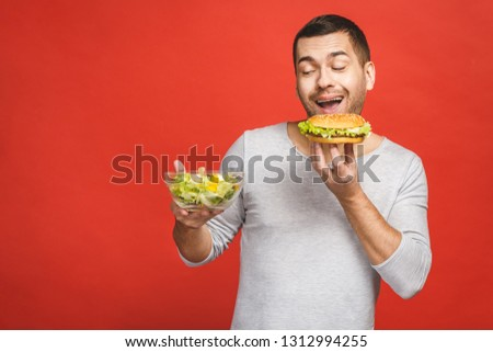 Man thinking choosing between salad and hamburger, healthy and junk food. Diet concept. Choosing between good healthy and bad unhealthy food. Organic food versus fast food, isolated over white.  #1312994255