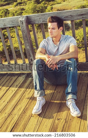 Man Thinking Outside. Wearing a gray T shirt, jeans, white sneakers, a young handsome guy is sitting on the wooden floor,  back against fence in a remote location, relaxing, thinking, lost in thought.