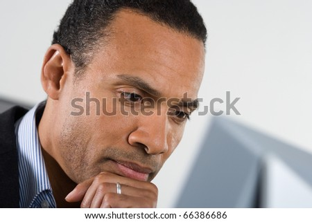 Man thinking with hand on chin while looking at computer