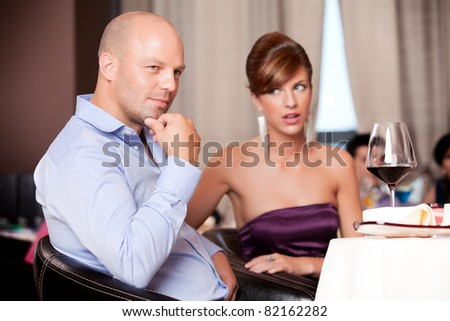 man thinking, woman suspicious at restaurant table