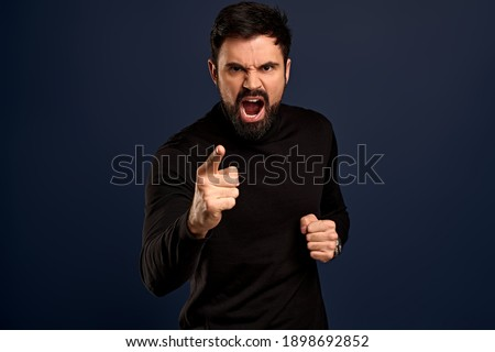 Man threatening person with angry outraged expression, lose temper standing distressed, pointing camera accuse someone, blame girlfriend, having argument and shouting, Blue background. Foto d'archivio ©