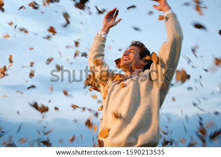 Man throwing autumn leaves in air