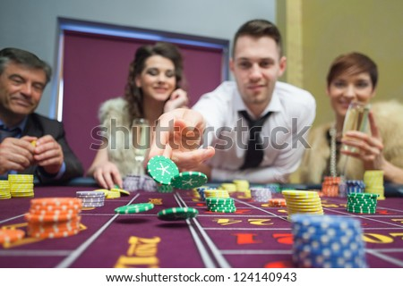 Man throwing chips down on roulette table in casino