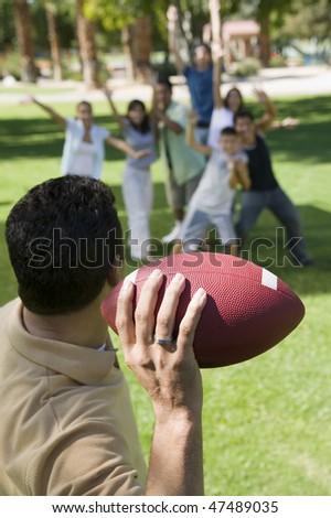 Man Throwing Football to Friends