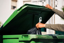 Man throwing out black eco-friendly recyclable trash bag in to big plastic green garbage container. Take out the trash