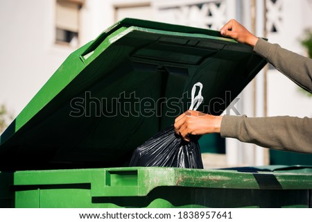 Man throwing out black eco-friendly recyclable trash bag in to big plastic green garbage container. Take out the trash Photo stock ©