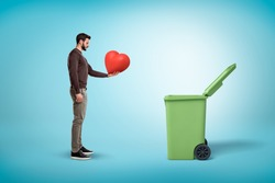 Man throwing red heart into open garbage bin on blue background. Digital art. People and objects. Trash and garbage.