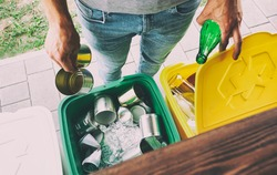 Man throwing the glass bottle and tin can into different dustbins for sorting trash