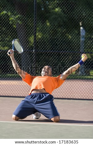 Man throws arms in the air while kneeling on a tennis court.  He is celebrating. Vertically framed photo.