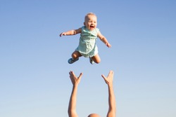 Man throws baby up against the blue sky. Concept game with children, happy family
