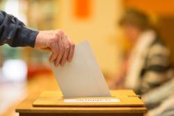 Man throws ballot papers into ballot box