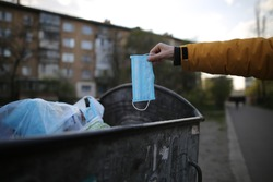 Man throws out a medical mask. Man throwing face masks into trash The used mask is cut to prevent reuse in the bucket. Medical face masks. Useless coronavirus face mask. Prevent the spread of the coro