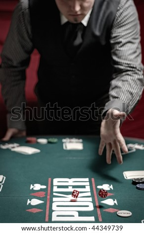 Man throws the dice on a poker table
