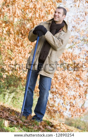 Man tidying autumn leaves in garden