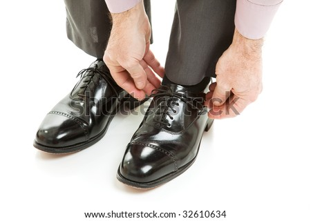 Man ties his shiney new black leather business shoes.  Isolated on white.