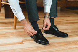 Man ties his shiney new black leather shoes.