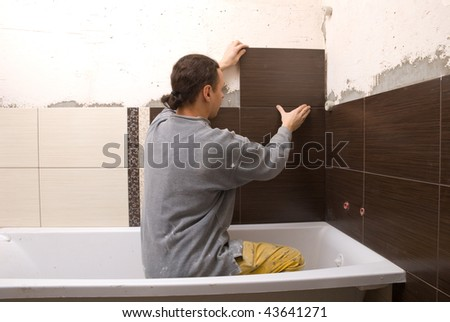 Man tiling a wall in the bathroom