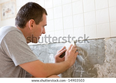 Man tiling a wall in the kitchen