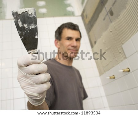 Man tiling the bathroom. Focused close up of hand holding putty knife or trowel. Man and background are out-of-focus. - stock photo