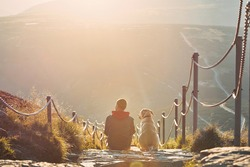 Man together with his dog sitting on pathway at sunset. View from Krkokonse Mountains, Czech Republic