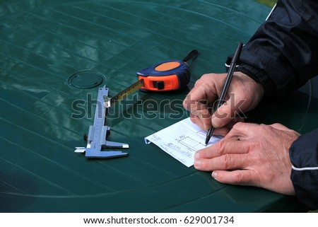 Man took measurements and draws schema of his idea on paper sheet.  Nearby is caliper and roulette.