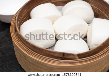 Man Tou, Soft and Hot Chinese steamed rolls serving on traditional bamboo steaming basket #1578300541