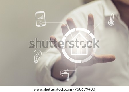Man touch smart home interface with icons providing control to temperature and lamps from mobile app