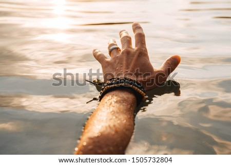 Man touches the water with his hand at sunset. Concept of freedom relaxation