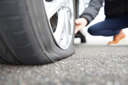 man touching a flat tire on the roadside