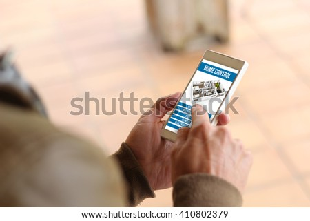 man touching the screen of his smartphone showing home automation app. All screen graphics are made up.