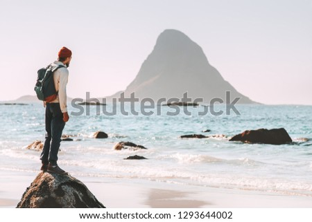 Man tourist enjoying sea and rock view on beach summer traveling in Norway  vacations outdoor lifestyle adventure trip escape solitude emotions #1293644002