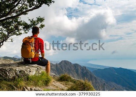 Man tourist hiker or trail runner looking at beautiful inspirational landscape in high mountains. Male runner with backpack, happiness and enjoying inspiring view on rocky top of mountain, Italy.