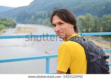 Man tourist in a yellow t-shirt with a backpack stands on a bridge over a mountain river in the background of mountain