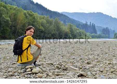 Man tourist in yellow t-shirt with a backpack sitting on the rocks on the dried river, in background mountains and river
