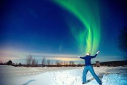Man tourist looks aurora northern lights night at forest, soft focus.