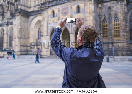 Man tourist selfie with phone camera in hands near the Prague Castle. Famous popular touristic place in the world. #743432164