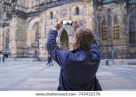 Man tourist selfie with phone camera in hands near the Prague Castle. Famous popular touristic place in the world. #743432170