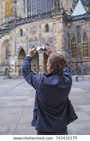 Man tourist selfie with phone camera in hands near the Prague Castle. Famous popular touristic place in the world. #743432179