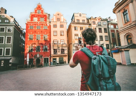 Man tourist sightseeing Stockholm city Gamla Stan landmarks traveling lifestyle girl taking photo by smartphone Europe trip summer vacations