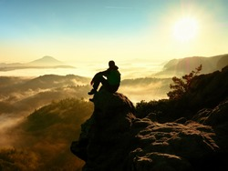 Man tourist sit on exposed rock. View point with heather and branches above misty valley. Sunny daybreak in rocky mountains.