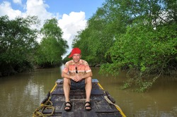 Man tourist sitting on boat floating in Mekong river, Vietnam