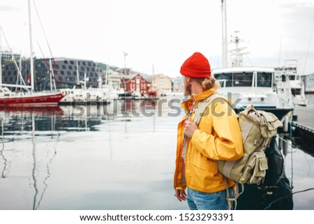 Man tourist with touristic rucksack wearing yellow jacket walking among authentic fishing boats. Hipster traveler wanderlust with  backpack explore scandinavian city