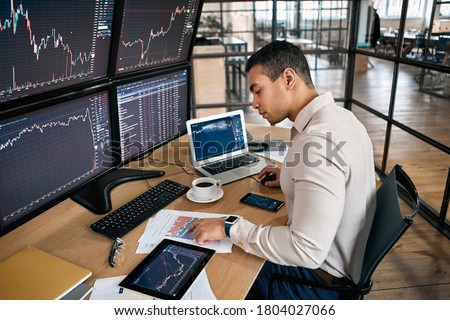 Man trader in formalwear sitting at desk in frot of monitors with charts and data at office browsing laptop checking documents analyzing stocks price changes concentrated drinking hot coffee trading Foto stock ©